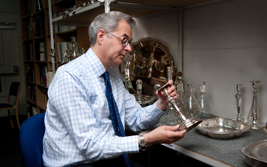 Harry Williams-Bulkeley examines a silver candlestick in a warehouse