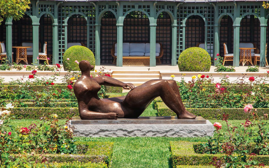 Henry Moore (1898-1986), Reclining Figure (conceived in 1982) in the rose garden at Jerry Perenchio's superb Bel Air estate. Estimate $8,000,000-12,000,000. Offered in the Impressionist & Modern Art