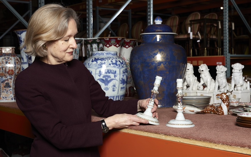 Specialist Becky MacGuire with a pair of Chinese export candlesticks with the arms of Philip V of Spain, circa 1725-30. 7¾ in (19.7 cm) high.