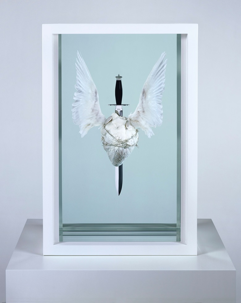 Damien Hirst (b. 1965) The Immaculate Heart ♥ Sacred, executed in 2008. Acrylic, painted stainless steel, stainless steel, resin, silicone, sterling silver barbed wire, monofilament, bulls heart, doves wings and formaldehyde solution. 36 x 24 x 11½ in (91.5 x 61 x 29.2 cm). Estimate £120,000-180,000. Offered in The George Michael Collection Evening Auction on 14 March 2019 at